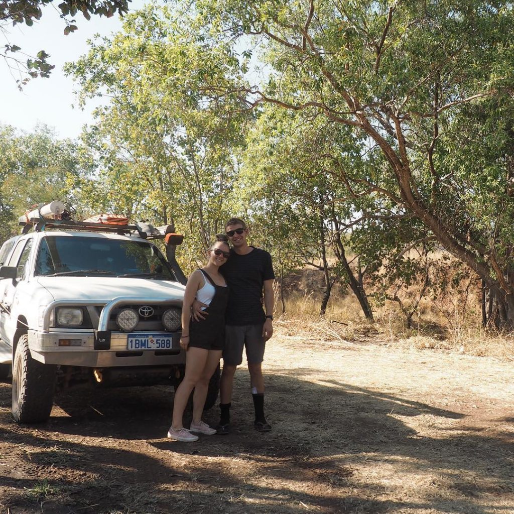 Girl and boy in bungle bungles purnululu national park smiling standing in front of car