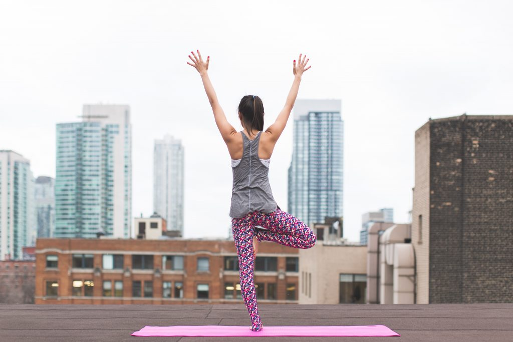 lady doing yoga on rooftop in city